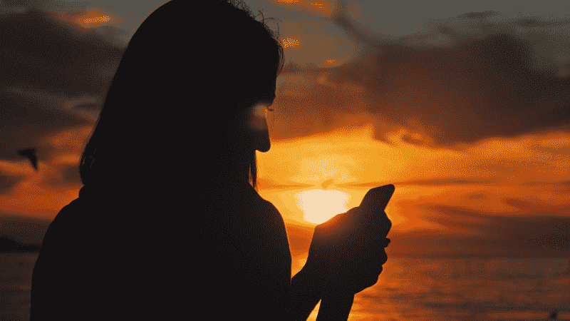 Person using cell phone at sunset